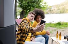 Multiracial Couple Taking Selfie Outside Van In Nature