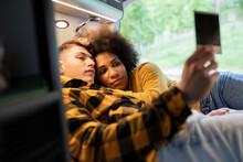 Multiracial Couple Examining Instant Photo In Van
