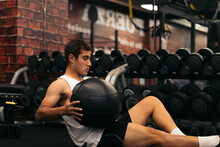 Young Man Doing Weight Ball Abs Exercise In A Gym