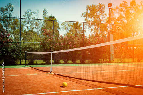 Wide angle photo of artificial grass tennis court with tennis ball during sunset Fototapet