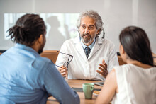 Senior Healthcare Worker Discussing With Couple. Male Doctor Is Showing Digital Tablet To Man And Woman. They Are Sitting In Hospital. Consultation In Doctors Office