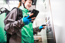 Happy Delivery Woman Using Smartphone In Elevator