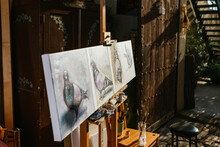Pigeons Painting On Canvas On Easel In Workshop