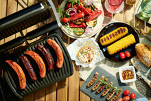 Upper View Of Table With Electric Grill And Grilled Sausages