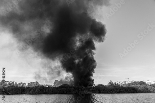 Wallpaper Mural A huge column of black smoke rises from a fire near the river
