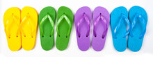 Four Pairs Of Multicolored Rubber Beach Flip Flops In A Row On A White Background, Isolate