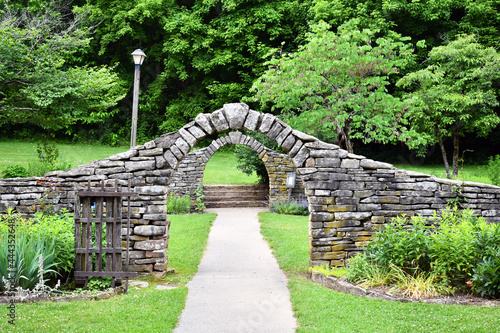 Leinwand Poster Stone walls and archways in a garden surrounded by verdant plants