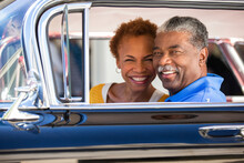 Older Couple Sitting In A Classic Car Looking To Camera Smiling