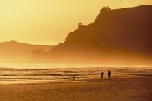Two People Enjoying Beach In Golden Light Of Dusk