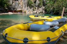Yellow, Inflatable Boat For Rafting Down The River. Active Rest In The Mountains, In Nature. Entertainment For A Group Of People. Canyon In The Background.