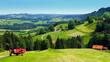 Blick auf grüne Landschaft bei Kranzegg im Allgäu mit Wiesen und Wäldern unter blauem Himmel
