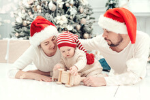 Happy Family Under Christmas Tree. Baby Boy In Santa Claus Hat With Gifts Under Christmas Tree With Many Gift Boxes Presents