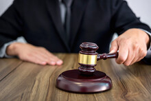 Male Lawyer Or Judge Hand's Striking The Gavel On Sounding Block, Working At Courtroom, Law And Justice Concept
