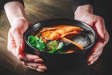 Pan Asian Food. Woman Hands Holding Tom Yam Soup In Black Bowl On Wooden Table Background