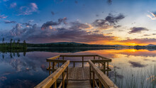 Panorama Of A Wooden Pier Leads Out Onto A Calm Lake With Forest On The Opposite Shore And A Colorful Sunset Sky
