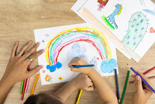 Top View Shot Of Mother And Daughter Are Drawing And Coloring Beautiful Rainbow Picture On Paper Together Shows Concept Of Art Playing Which Enhance Creativity, Learning And Enjoyment For Child.