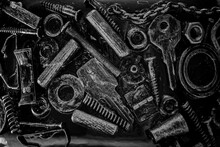 Many Small Spare Parts And Parts On A Black Background. Steampunk Style. Black And White Photo.