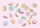 Sweet delicious macarons flying on pink background