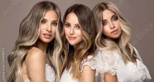 Three beautiful girls in white wedding dresses with hair coloring in ultra blond. Stylish hairstyle curls done in a beauty salon. Fashion, cosmetics and makeup.Adorable brides