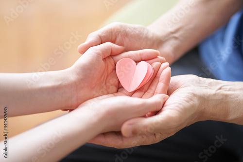 Fototapeta ハートのオブジェを持つ介護士と高齢者の手元