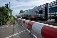 Selective Focus View At Red And White Level Crossing Railway Barrier Which Block The Road And Regional Train Move On The Rail On Countryside In Germany.
