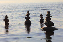 Stones In The Water Are Stacked In Pyramids. Image On The Topic Of Balance And Peace Of Mind