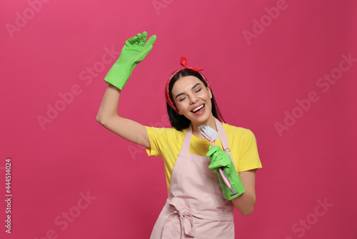 Young housewife with brush on pink background Fotobehang