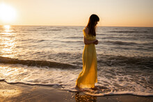 Beautiful Woman On The Beach At Sunset. She Is Enjoying Serene Ocean Nature During Travel Holidays Vacation Outdoors. Summer Time.