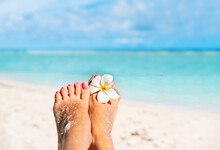 Relaxing Bare Female Feet With White  Frangipani Flower By The Water On Sea Shore, With Copy Space