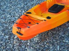 Orange Single Seater Sea Kayak For Fishing On The Pebble Seashore