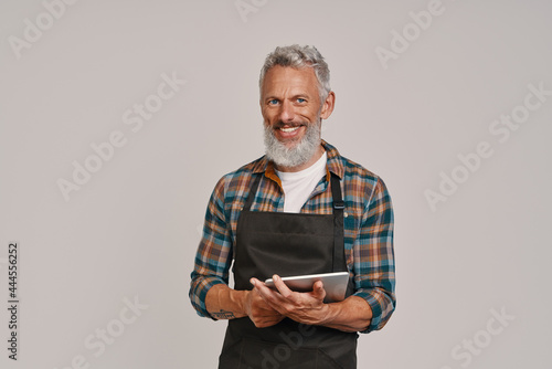 Canvas Senior man in apron smiling and using digital tablet while standing against gray