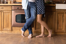 Legs Of Young Barefooted Couple Standing On Heat Floor In Kitchen At Home With Wooden Furniture And Vintage Appliance In Background. Man And Woman Enjoying Being Together In New Apartment. Close Up