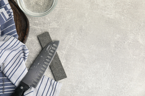 Tela Sharpening stone, knife and water on grey table, flat lay