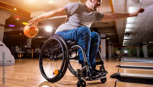 Fotografiet Young disabled man in wheelchair playing bowling in the club