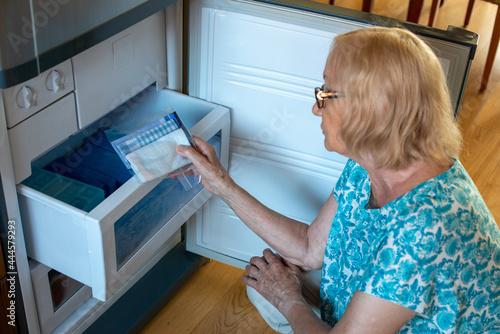Fotografia Senior woman putting handkerchiefs in the fridge freezer