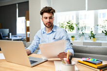 Young Man Browsing Documents While Working From Home Office