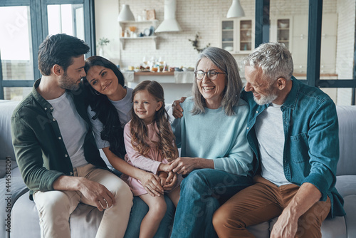 Fototapeta Happy family spending time together and smiling while sitting on the sofa at hom