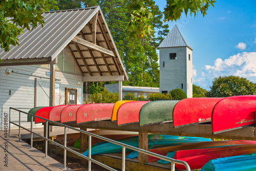 Foto A view of colorful canoes by a boathouse with a viewing tower in the background