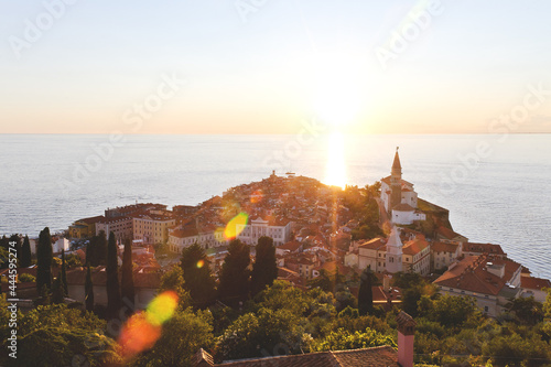 Scenic view of red roofs of the historical center of old town Piran with main church against the sunset sky and blue Adriatic sea. Aerial view, coast of Slovenia.