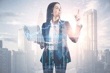 Happy Young European Businesswoman In Suit Holding Tablet And Pointing Up On Abstract Bright City Background With Forex Chart And Mockup Place. Finance, Trade And Success Concept. Double Exposure.