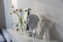 A Bunch Of Fluffy Dandelions In A Chemical Flask, An Empty Photo Frame, A Cup Of Espresso Coffee, And A Plaster Head Of David On A White Chest Of Drawers.