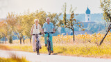 Senior couple, woman and man, riding their bikes along field of sunflowers
