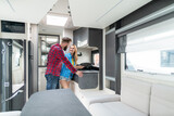 Woman and man testing interior of camper they want to buy or rent checking the kitchenette