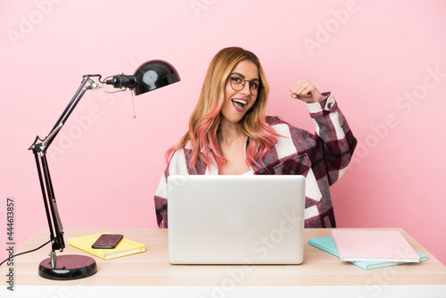 Fotografering Young student woman in a workplace with a laptop over pink background celebratin