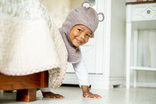 Sweet African American Baby Boy In Cute Hat With Ears Crawling, Peeking Out From Behind The Bed And Smiling, Playing Hide And Seek Game, Pretending He Is Bear