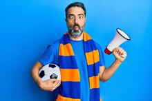 Middle Age Man With Beard And Grey Hair Football Hooligan Holding Ball And Using Megaphone Making Fish Face With Mouth And Squinting Eyes, Crazy And Comical.