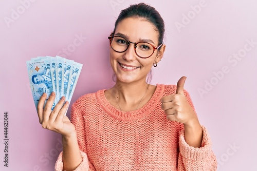 Fényképezés Young caucasian woman holding 50 thai baht banknotes smiling happy and positive,