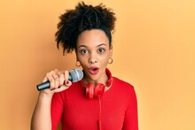 Young African American Girl Singing Song Using Microphone And Headphones Scared And Amazed With Open Mouth For Surprise, Disbelief Face