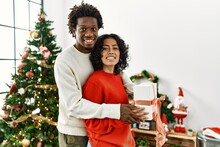 Young Interracial Couple Smiling Happy And Hugging Holding Christmas Gift At Home.