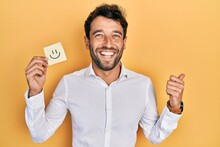 Handsome Man With Beard Holding Smile Emoji Reminder Pointing Thumb Up To The Side Smiling Happy With Open Mouth